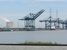 Een mooie uitkijk aan de kant van het kanaal met daar in de verte de werkkranen van de haven